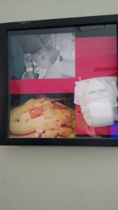 A shadow box with 2 pictures and a diaper