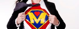 Super mom, NICU, advocate, Woman wears a superhero style t-shirt under her business suit