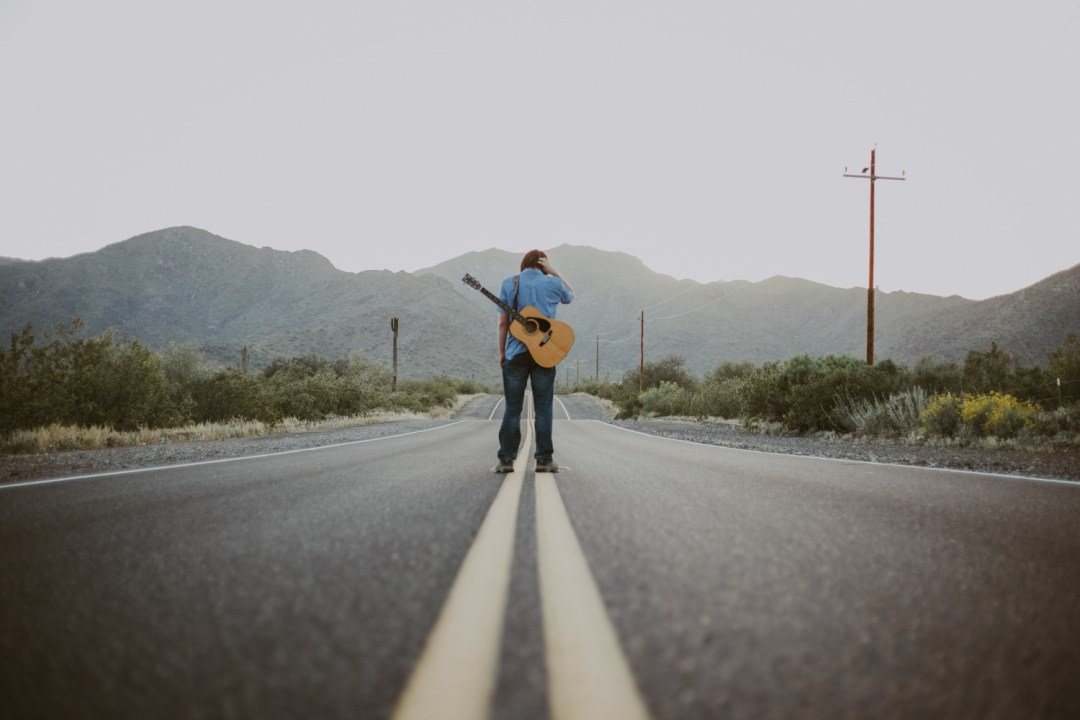 professional-branding-photographer-Advertising-photography-imagery-in-west-phoenix-arizona-with-young-musician-hitch-hiking-his-way-to-stardom-with-white-tank-mountains-in-the-background