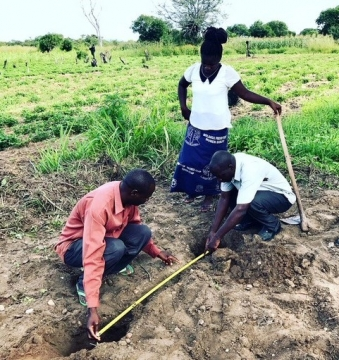 Seminary students Nellas, Tryson and Sylvester take measurements for the construction if a tippytap hand washing station at Chasefu Farm.