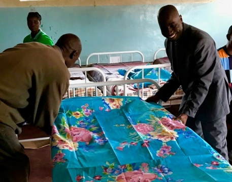 CCAP Synod of Zambia General Secretary Rev. Sevatt Kabaghe helps make up the new beds at Egichikeni Rural Health Center.