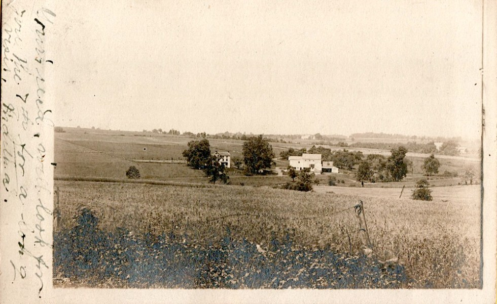 old black and white postcard has a handwritten note on the left-hand edge. The postcard image is a long view across a field of a farm in the distance.