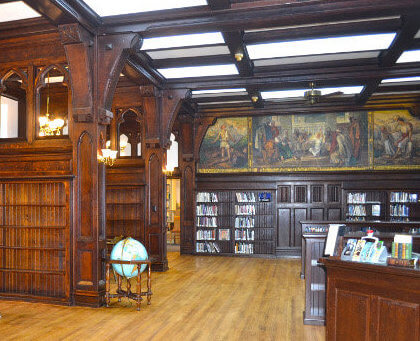 the school library features woodwork and painted murals