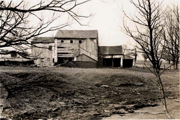 black and white photo of dilapidated barn buildings