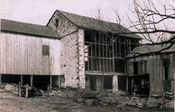 black and white photo shows a barn with all siding removed, revealing the wooden stud framing