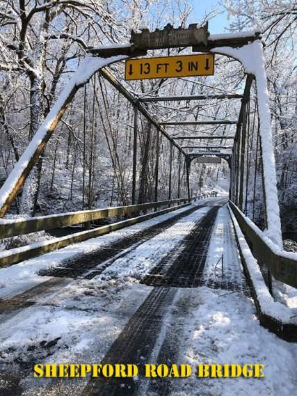 A metal bridge with its tracery details with a coating of snow
