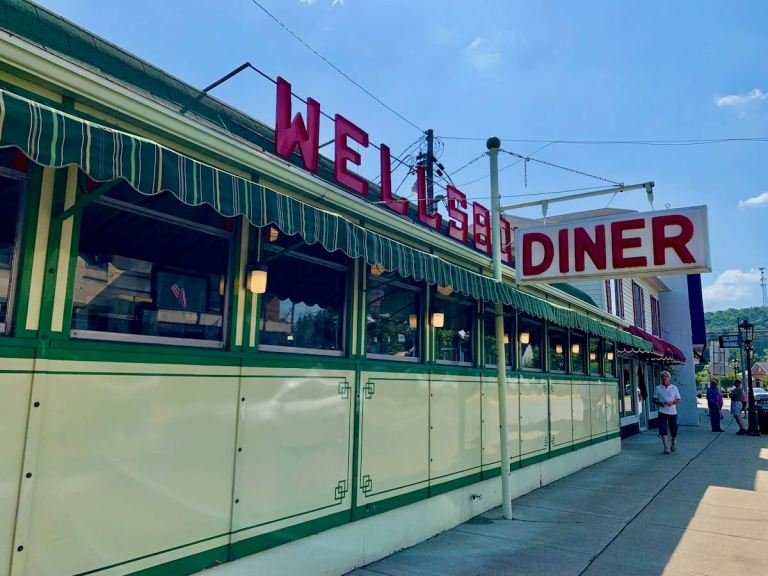 Exterior angled view of the vintage Wellsboro Diner, its yellow and green panels contrasting with the restaurant signage in red.
