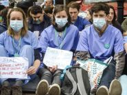 Junior doctors in scrubs and masks sit down in a silent protest outside Bristol Royal Infirmary.