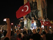Erdogan supporters wave Turkish flags in Taksim Square (AP)