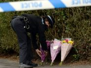 A police officer lays flowers at the scene in Campsall, South Yorkshire
