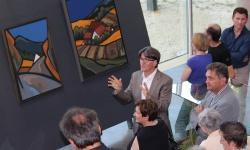 """Vernissage im Haus zur Wildnis: Herbert Muckenschnabl (Mitte) führt durch seine Ausstellung """"Bilder aus dem Alltag""""; begleitet von Nationalparkleiter Franz Leibl (rechts). (Foto: NPV Bayerischer Wald)"""