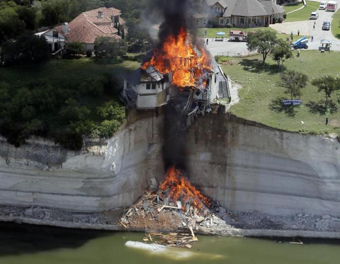 Smoke rises from a house deliberately set on fire, days after part of the ground it was resting on collapsed into Lake Whitney