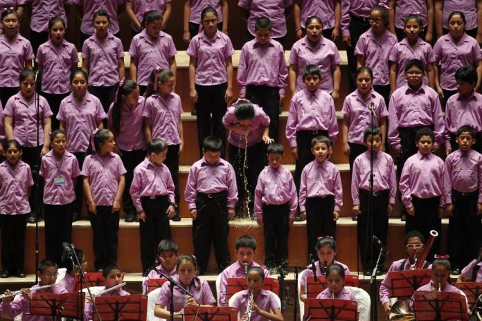 """A young member of the choir of """"Sinfonia por el Peru"""" vomits before performing with Peruvian tenor Juan Diego Florez at Lima's National Theatre"""