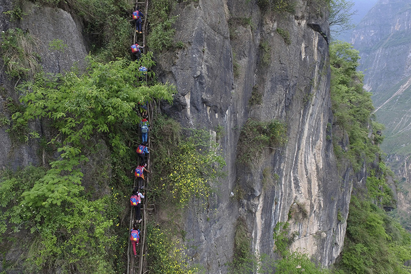 Children climb on a cliff on their way home from school in  Sichuan province.
