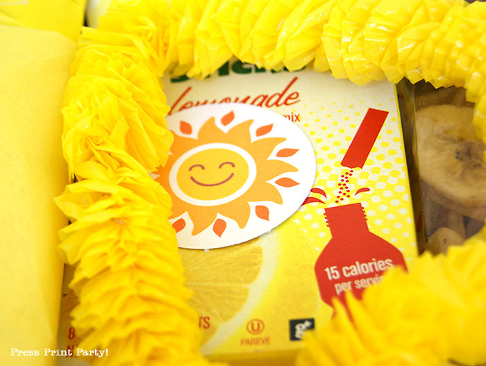 Yellow lei and lemonade with happy sun tag