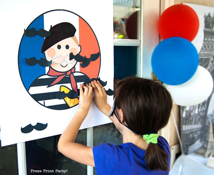 Girl playing Pin the mustache on the French guy free printable game for french or paris party. Press Print Party!