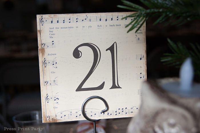table number with music sheet. Rustic Christmas table centerpiece with greenery, rustic owl, white mason jar, pinecones, and berries. With a free music sheet table number printable download. With a brown tablecloth and music sheet place mats. Easy and cheap. by Press Print Party!