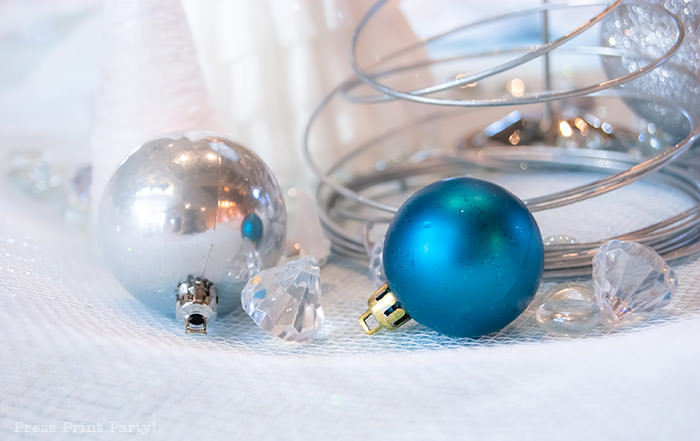 Christmas bulbs silver and blue with christmas wire tree and confetti. For Christmas table decor ideas blue and silver winter wonderland decorations. Christmas tablescape for large event christmas party, diy holiday table setting. by Press Print Party!