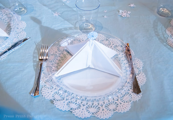 table setting with a tree napkin and a snowflake topper on a lace doily white For Christmas table decor ideas blue and silver winter wonderland decorations. Christmas tablescape for large event christmas party, diy holiday table setting. by Press Print Party!