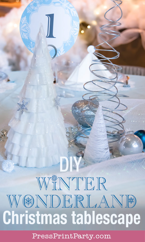 coffee filter tree, wire christmas tree and string tree on table with blue tablecloth For Christmas table decor ideas blue and silver winter wonderland decorations. Christmas tablescape for large event christmas party, diy holiday table setting. by Press Print Party!