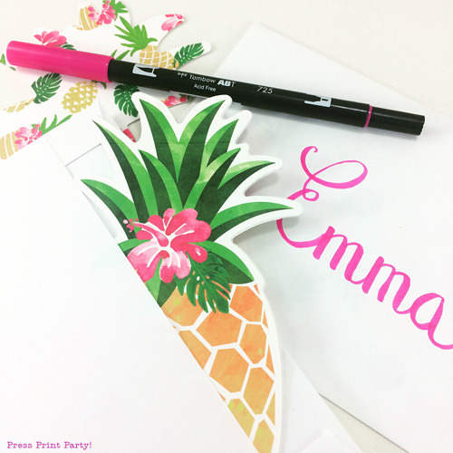Pineapple party invitation in an envelope with a pink towbow pen