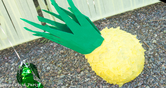 Pineapple pinata on the ground with a yellow streamer body and green top. Press Print Party!