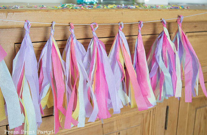 multicolored tissue paper tassels on mantel
