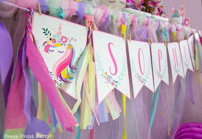 Unicorn banner with rainbow tassels.