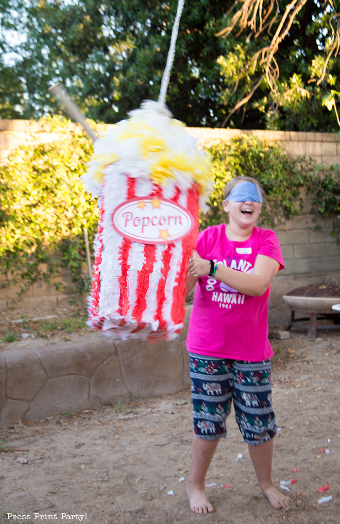 Girl hitting a popcorn box pinata - Press Print Party!