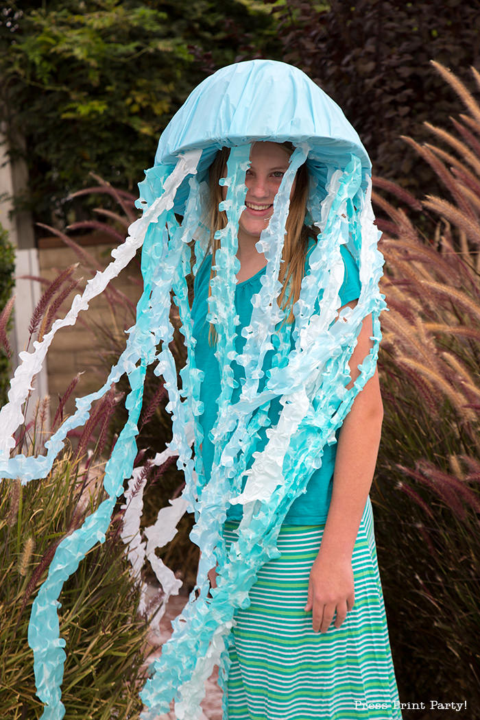 Girl with jellyfish costume for Halloween. Blue and white tentacles. light up halloween costume. easy jellyfish costume diy. easy. Press Print Party!