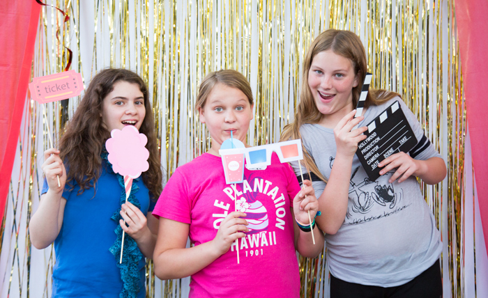 movie party photo booth with fun props. 3 girls having fun with props at a movie night party. Gold shimmering background and red curtains