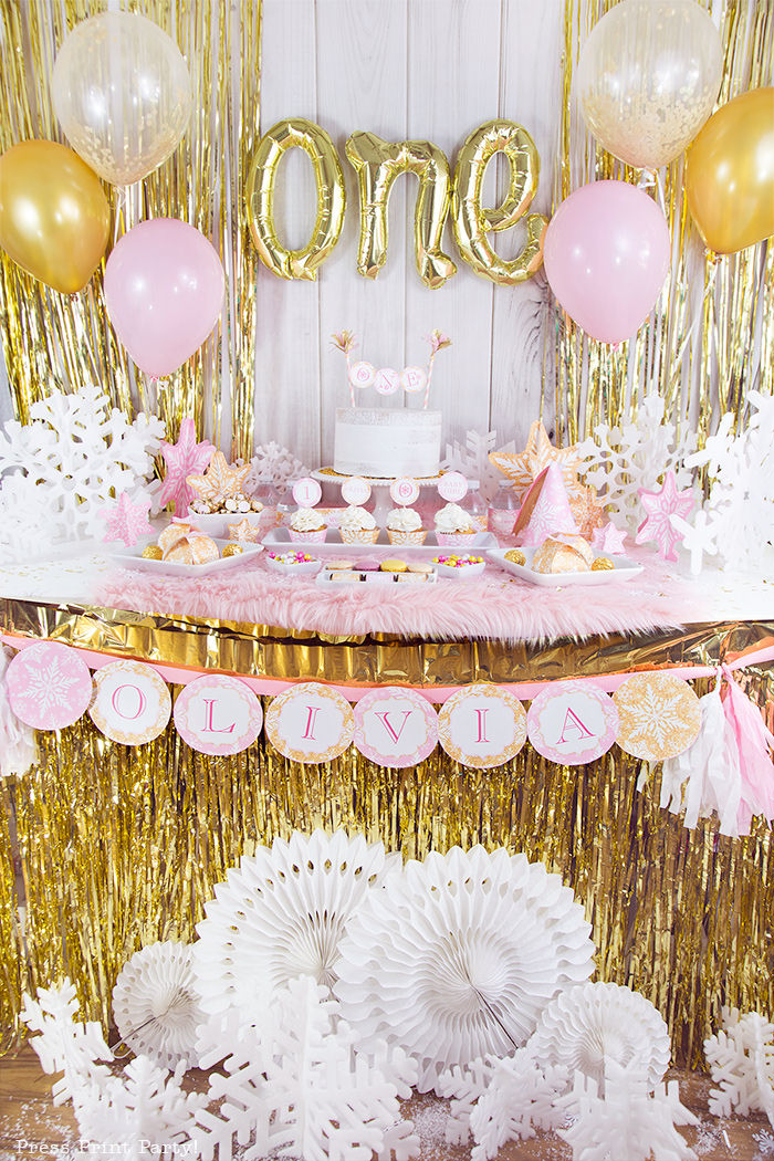 winter onderland first birthday girl party pink and gold decorations dessert table with onederland cake and cupcakes, printable snowflakes, favor boxes and chocolates, one inflatable balloons, pink and gold balloons and gold fringe backdrop - Press Print Party!