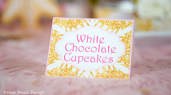snowflakes place card, gold with pink lettering saying white chocolae cupcakes winter onederland gold and pink snowflakes kisses with printable labels winter onderland first birthday girl party pink and gold dessert table with onederland cake and cupcakes, printable snowflakes, favor boxes and chocolate - Press Print Party!