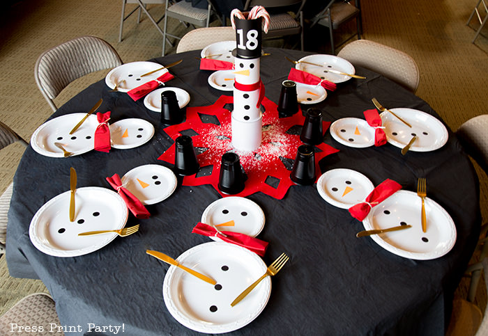 cute Christmas snowman table decor made with cans and felt scarf on a table with snowman made out of white plates - Press Print Party!