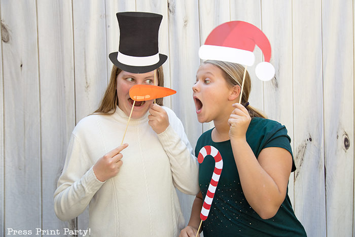 2 girls with Christmas photo booth props printables, one with a snowman hat and carrot nose, the other with santa hat and candy cane - Press Print Party!