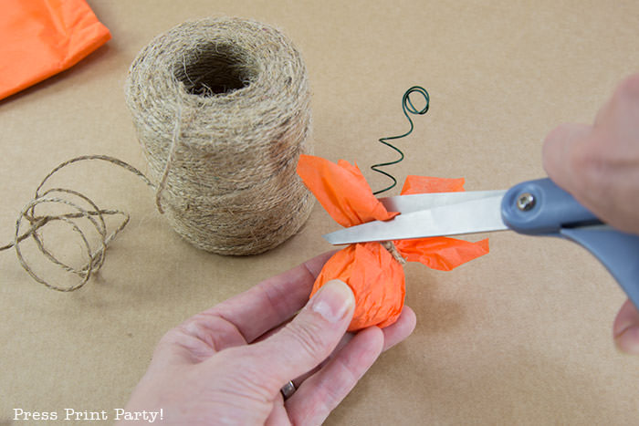 Cutting the excess tissue paper on the pumpkin place card holder Press Print Party!