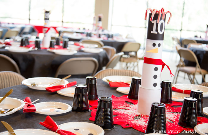 cute Christmas snowman table decor made with cans and felt scarf on a table with snowman made out of white plates church dinner decorations- Press Print Party!