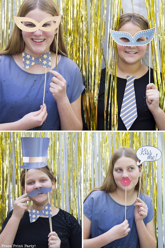 2 girls having fun with new year's eve photo booth props. Party hat, bowtie, mask, kiss me speech bubble, hat, mustache - Press Print Party!