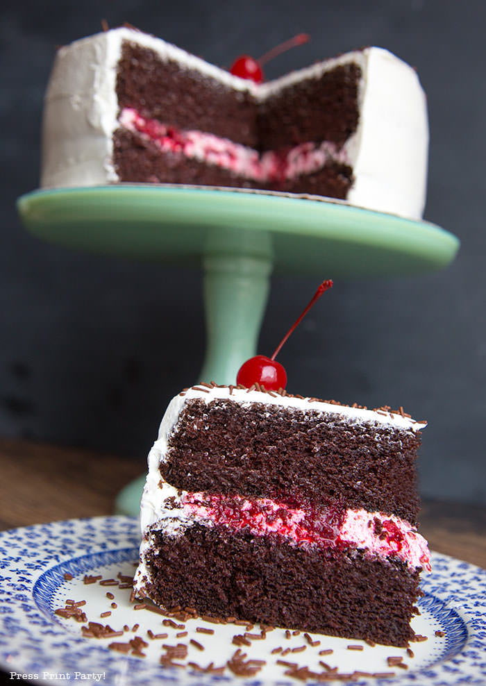 Moist chocolate cake with white frosting and berry filling on a green pedestal with a cherry on top and a piece of cut cake in the foregroud- Press Print Party!