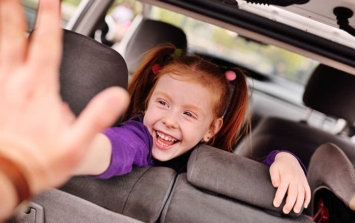 girl laughing in car playing a game - fun games to play in the car