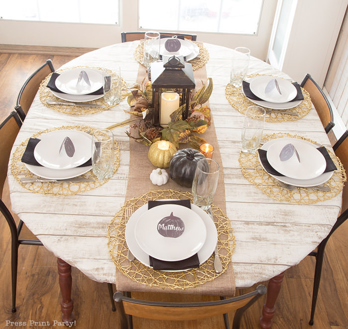 Golden Farmhouse Decorations for Thanksgiving Table. Get inspired with Thanksgiving table decor ideas. White wooden walls with gilded wreath and gold chargers, white plates, black pumpkin place cards, black lantern, golden pumpkins, votives, decorations for thanksgiving table, farmhouse decor ideas, Friendsgiving ideas, thanksgiving table decor, Thanksgiving table setting - tablescape. Press Print Party!