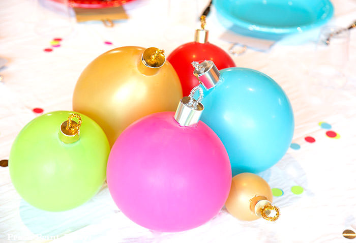 close up of large ornament christmas centerpiece with ballons. Balloons with ornament toppers in green, gold, blue, red and hot pink. Christmas tablescape balloon centerpiece decoration with large ornament balloons and plates that look like ornaments. Very cheery and bright. Fun and creative for your Christmas party. Simple Christmas balloon decor ideas diy. Press Print Party!