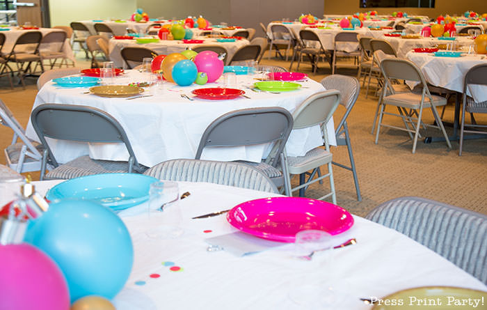 Christmas table centerpiece. Balloons with ornament toppers in green, gold, blue, red and hot pink. Christmas tablescape balloon centerpiece decoration with large ornament balloons and plates that look like ornaments. Very cheery and bright. Fun and creative for your Christmas party. Simple Christmas balloon decor ideas diy.