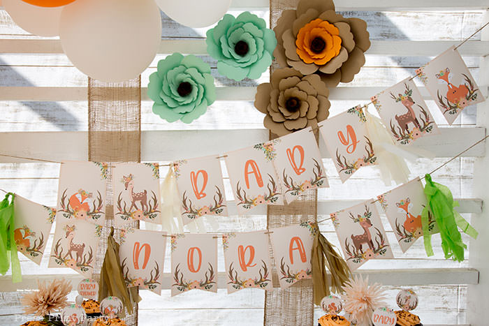 Woodland baby shower banner printable with paper flowers backdrop with white wood and burlap. Woodland animals Baby Shower Theme with woodland creatures and forest animals party supplies. Woodland decoration girl baby shower ideas. Can be used for woodland birthday party. Rustic forest animals with flowers and antlers. Fox baby shower, Deer baby shower.