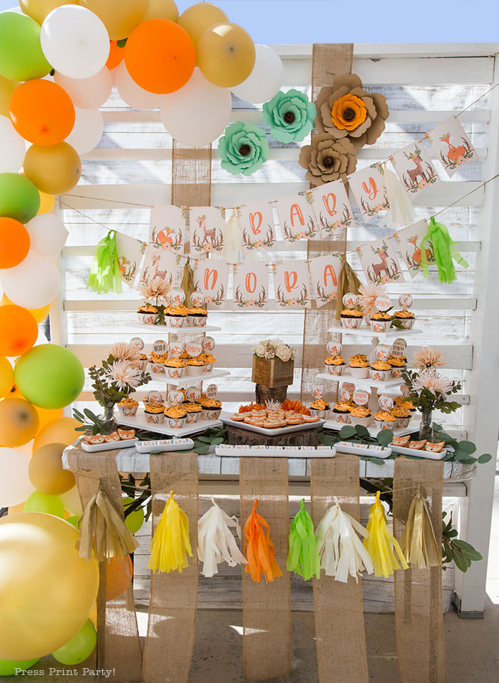 woodland baby shower ideas dessert table backdrop. with organic balloon garland in gold, orange, white and green. cupcakes and banner printables fox macarons, paper tissue tassels and woodland paper flowers. food ideas. Woodland animals Baby Shower Theme with woodland creatures and forest animals party supplies. Woodland decoration girl baby shower ideas. Can be used for woodland birthday party. Rustic forest animals with flowers and antlers. Fox baby shower, Deer baby shower.