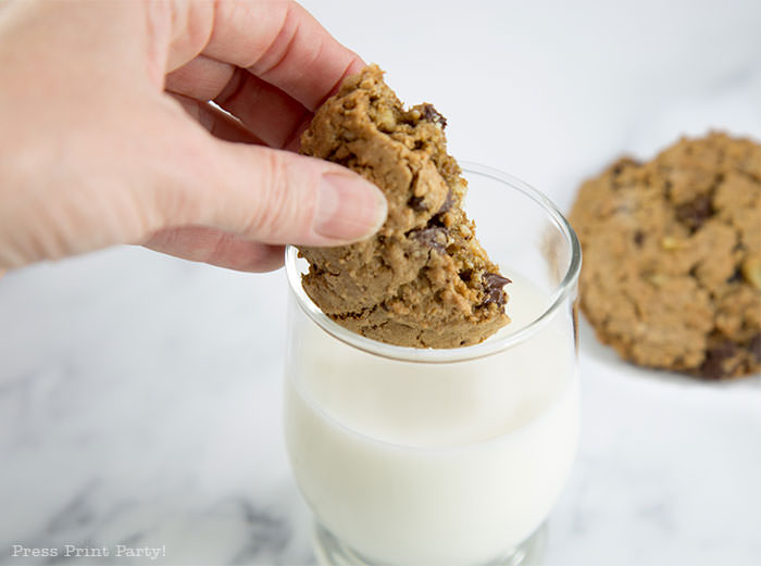 best ranger cookies recipe. chocolate chips and rice krispies cookies being dunked in milk.