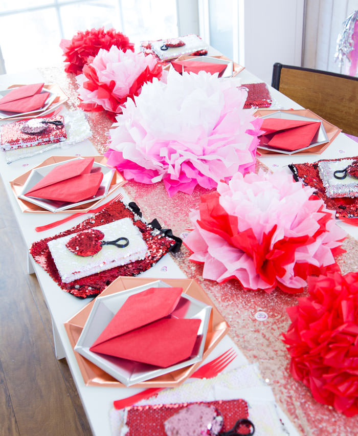 Galentines day or valentines day table decorations with tissue paper flowers in pink and red and red heart napkins and flip sequins favors - Galentine's Day Party Ideas for Teens - Press Print Party!