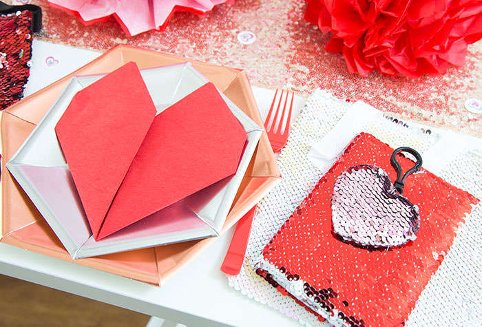 Red heart napkin fold on rose hexagonal metallic plate and silver plate -Flip sequins bag with flip sequins notebook and flip sequins heart clip keychain as party favor ideas- Galentine's Day Party Ideas for Teens - Press Print Party!