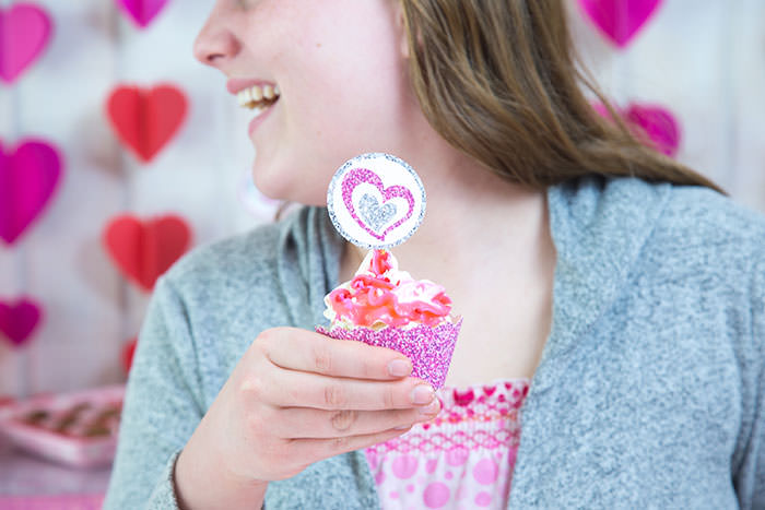 Girl having fun for Galentine's or Valentine's day with glitter heart free cupcake wrappers printables - Press Print Party!