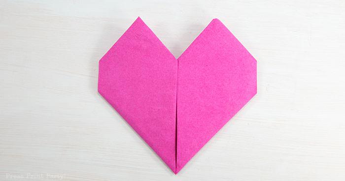 Heart Fold Napkin instructions- How to fold a napkin like a heart - paper napkin or cloth napkins - By Press print Party. Pink paper napkin folded like a heart DIY tutorial